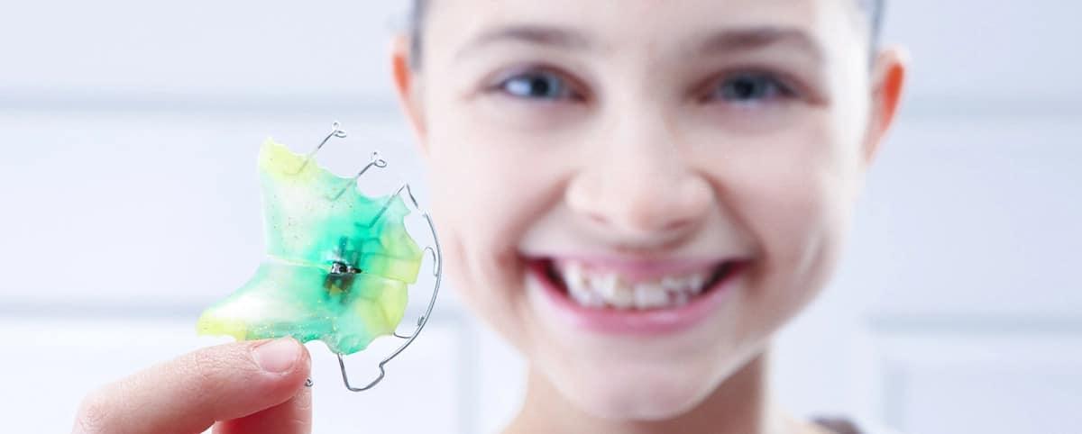 Lächelndes Mädchen mit loser Zahnspange in der Hand