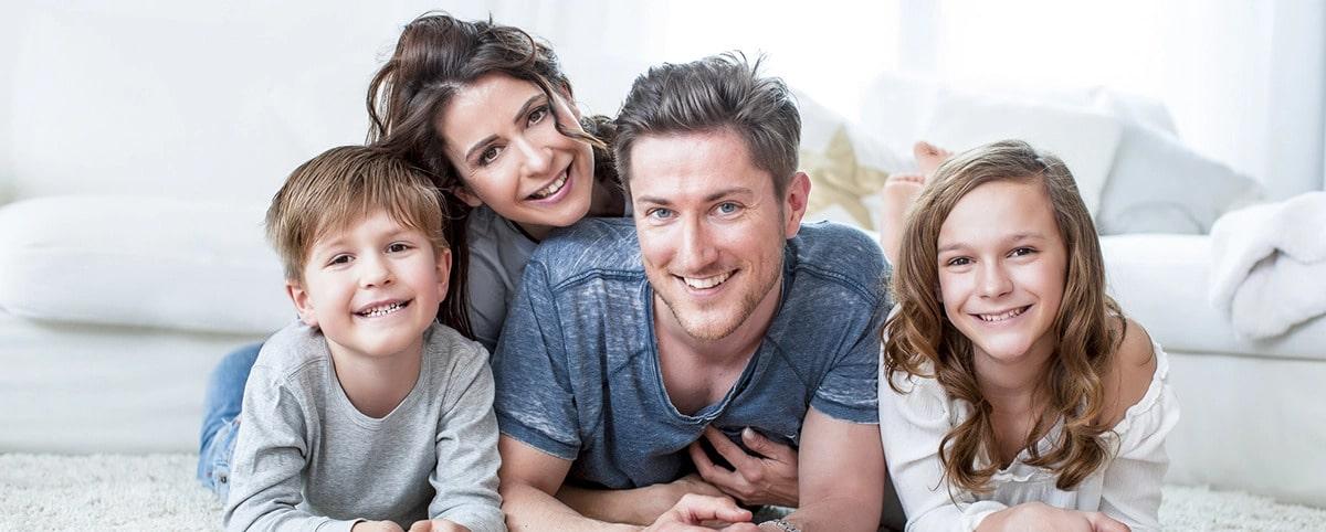 Glückliche, lächelnde Familie mit weißen Zähnen, die zufrieden mit Ihrer Prophylaxe bei Dr. Moroni sind