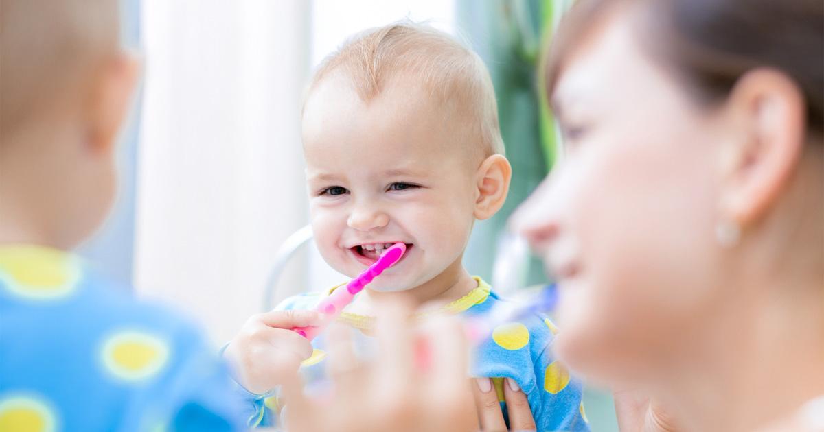Baby und Eltern am Zähneputzen