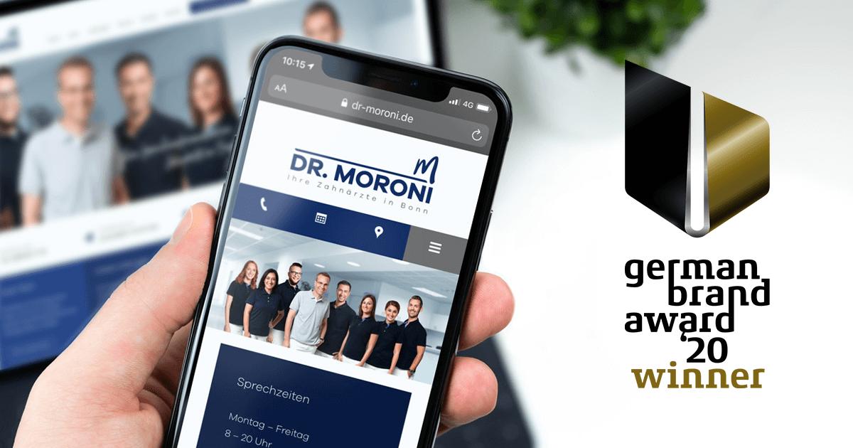 Dr. Moroni Website auf einem Smartphone neben dem German Brand Award 20 Winner Logo