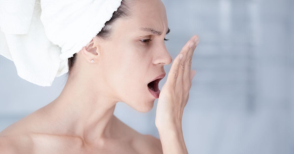Frau, die skeptisch schaut und kontrolliert, ob sie Mundgeruch hat