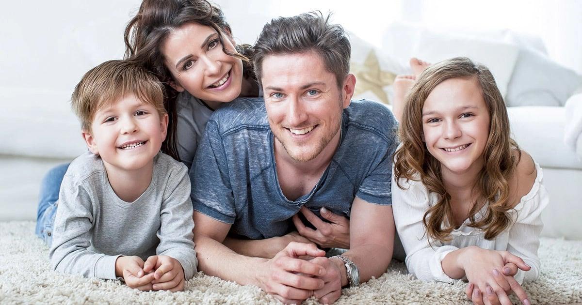 Glückliche, lächelnde Familie mit weißen Zähnen, die zufrieden mit Ihrer Prophylaxe sind